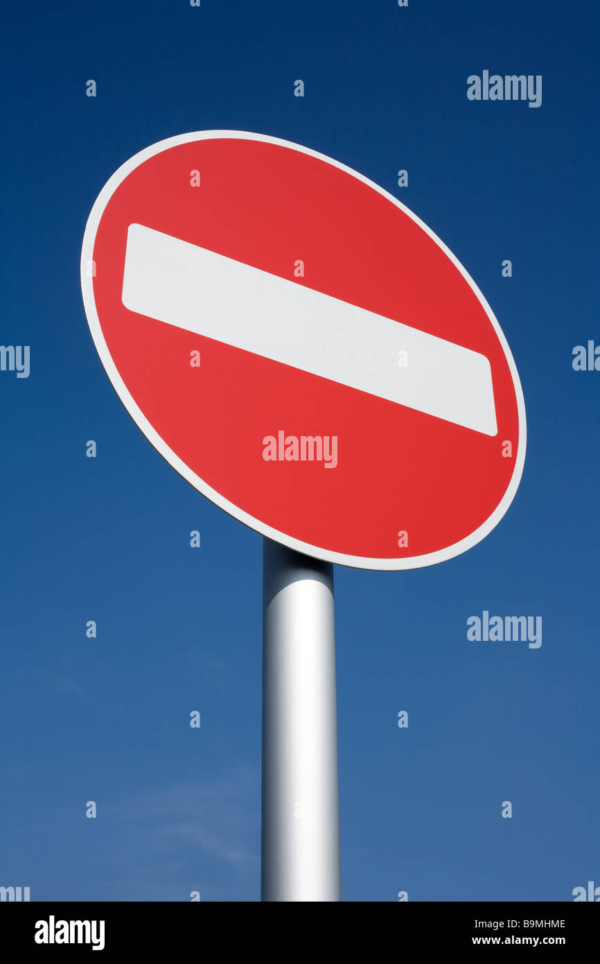 British red and white no entry road sign with a blue sky. - Stock Image