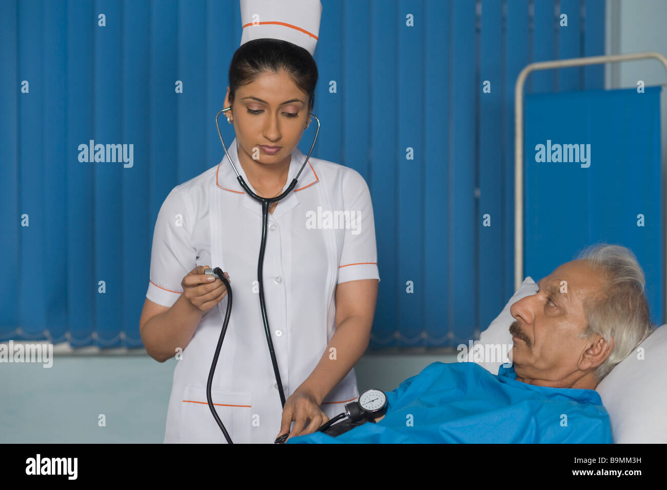 Female nurse checking a patient's blood pressure - Stock Image