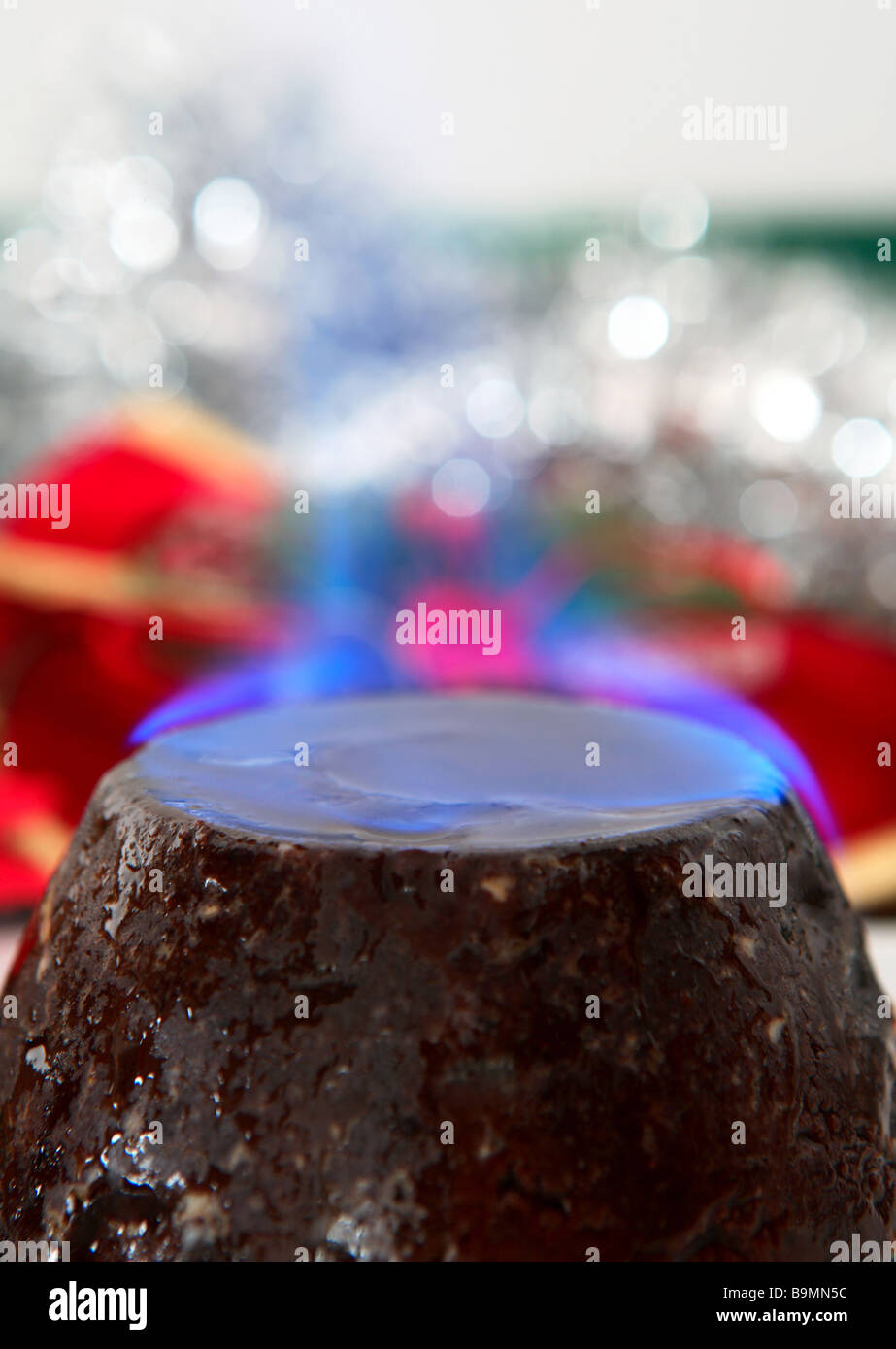 A traditional christmas pudding,smothered in brandy and set alight,with a background of festive  glitter. Stock Photo