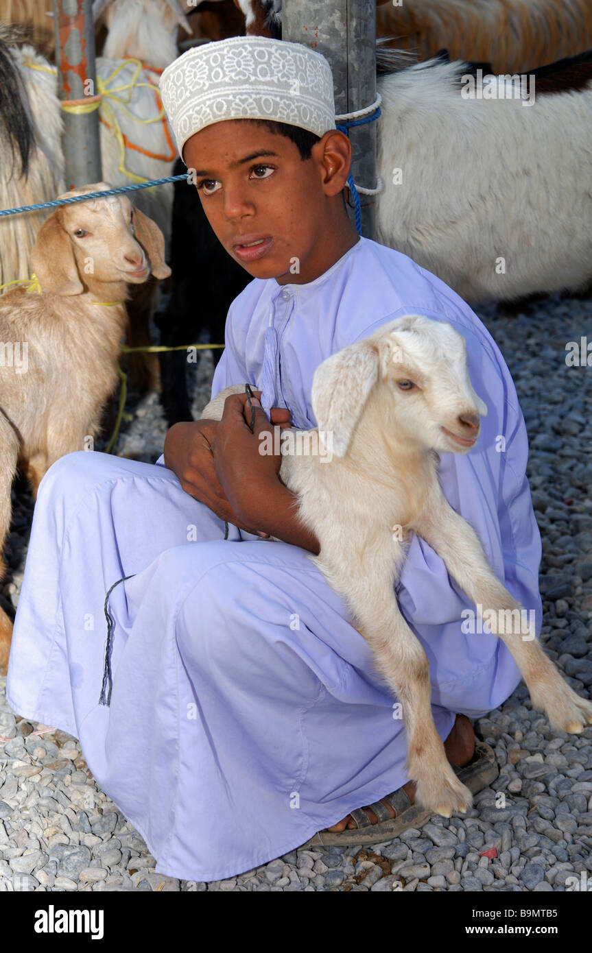 Worried Omani boy tenderly holds a goatling in his arms, Nizwa, Sultanate of Oman Stock Photo