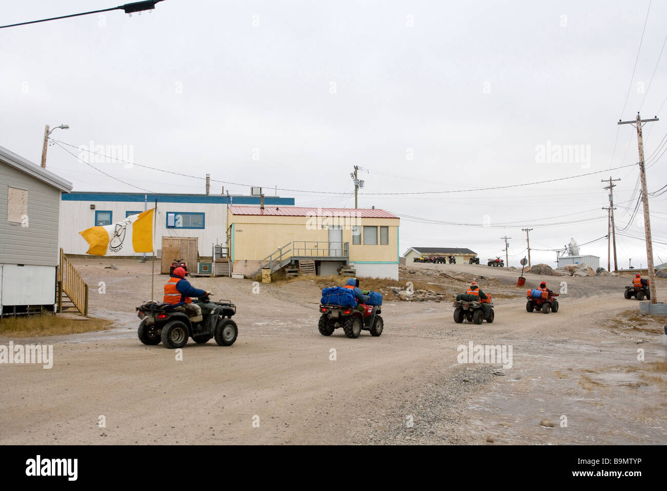 Dirt track with row of Canadian Rangers leaving on quad bikes, Canadian Arctic, Canada Stock Photo