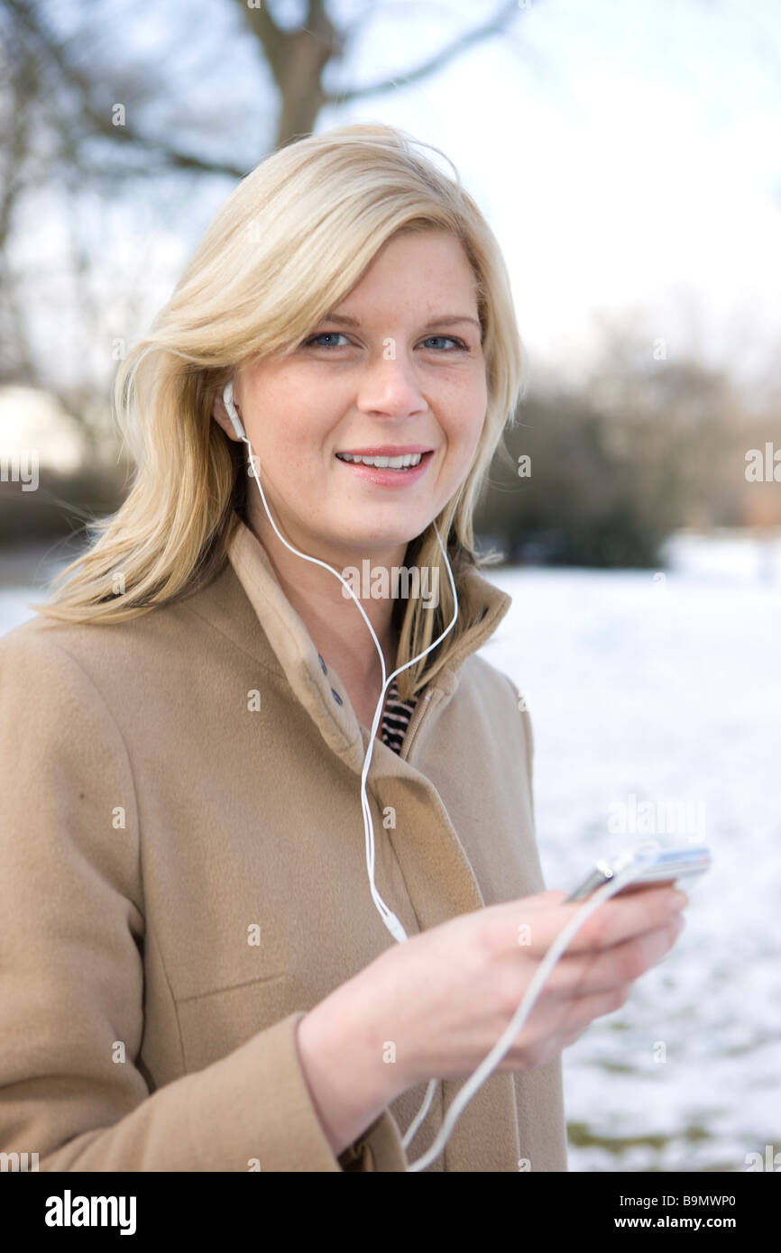 frau mit i pod im winter beim spaziergang - Stock Image