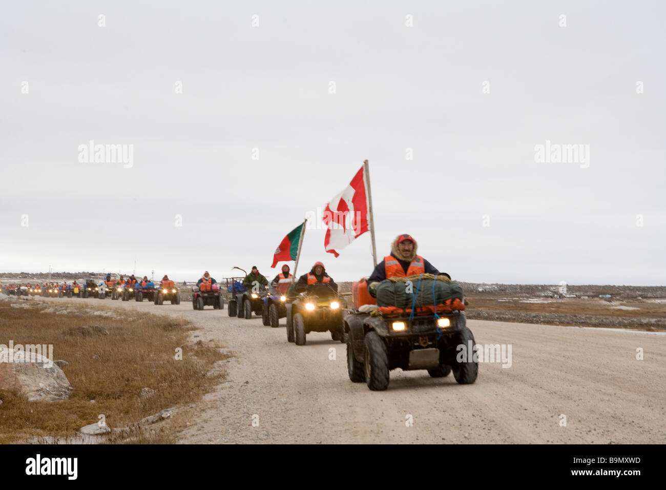 Dirt track with row of Canadian Rangers and canadian flag on quad bikes, Canadian Arctic, Canada - Stock Image
