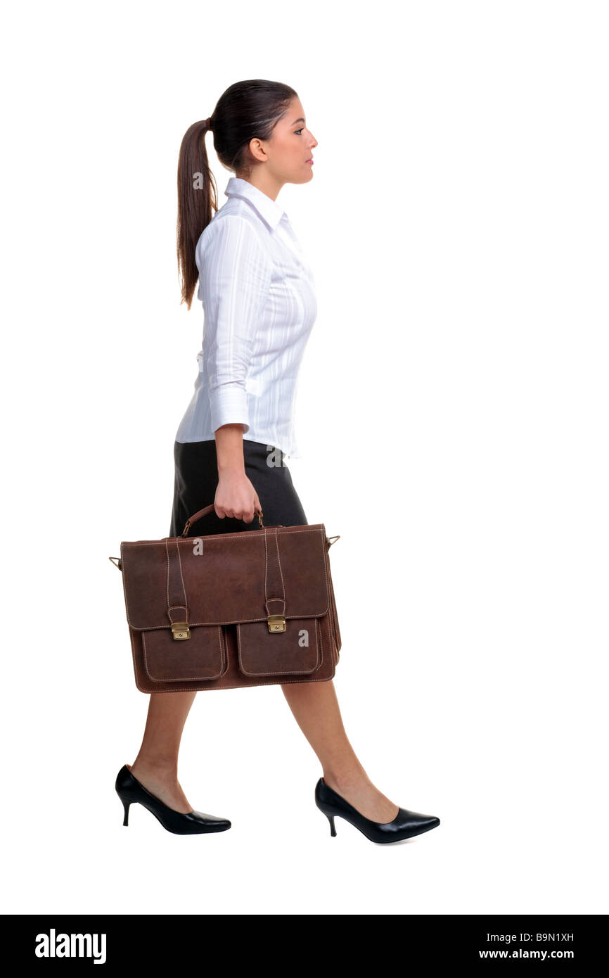 Young attractive businesswoman walking along carrying a brown leather briefcase isolated on white background - Stock Image