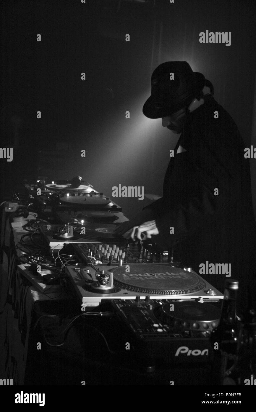 Moody shot of a DJ playing in a dark night club, black and white - Stock Image