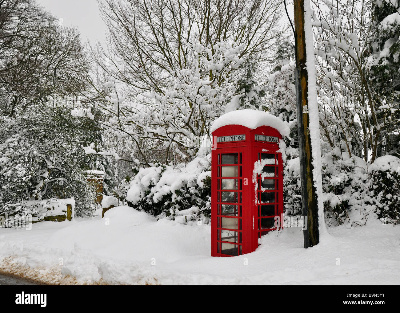 Old rural red telephone box in deep snow - Stock Image