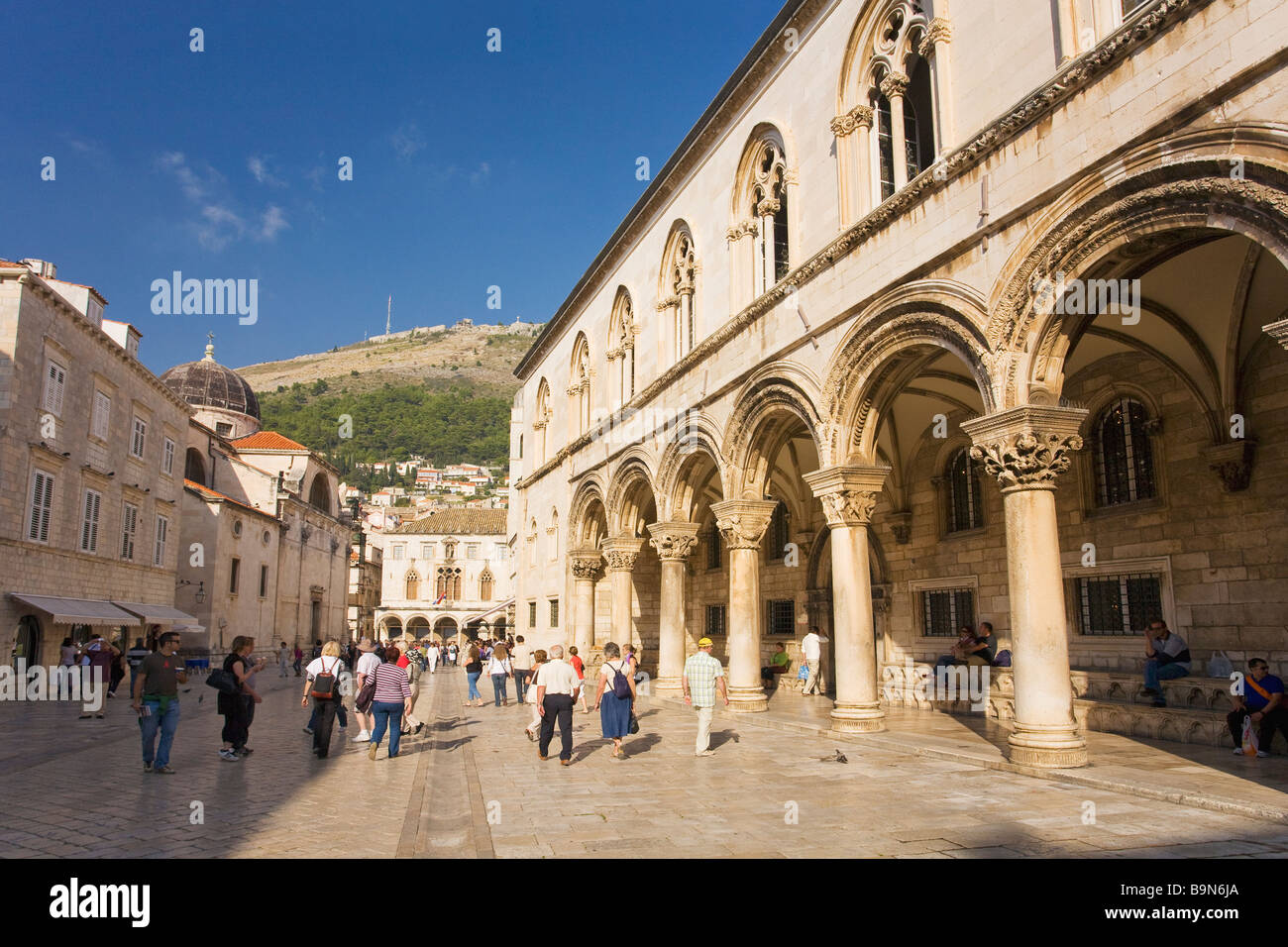 Tourists and visitors stroll outside the Rectors Palace in the walled city of Dubrovnik in summer sunshine Dalmatian - Stock Image