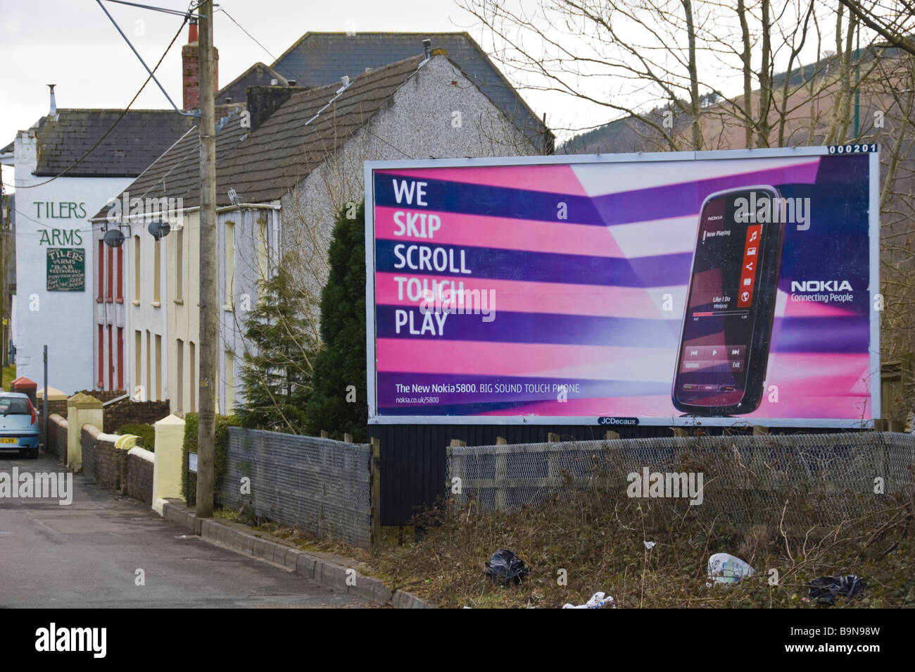 JCDecaux advertising billboard for Nokia mobile phone at end of terrace of houses Blaina in South Wales Valleys - Stock Image