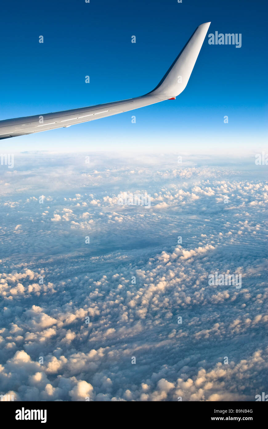 View through airliner window high above clouds - Stock Image