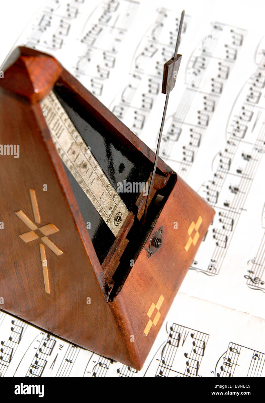Old German metronome sits on top of sheet music. - Stock Image