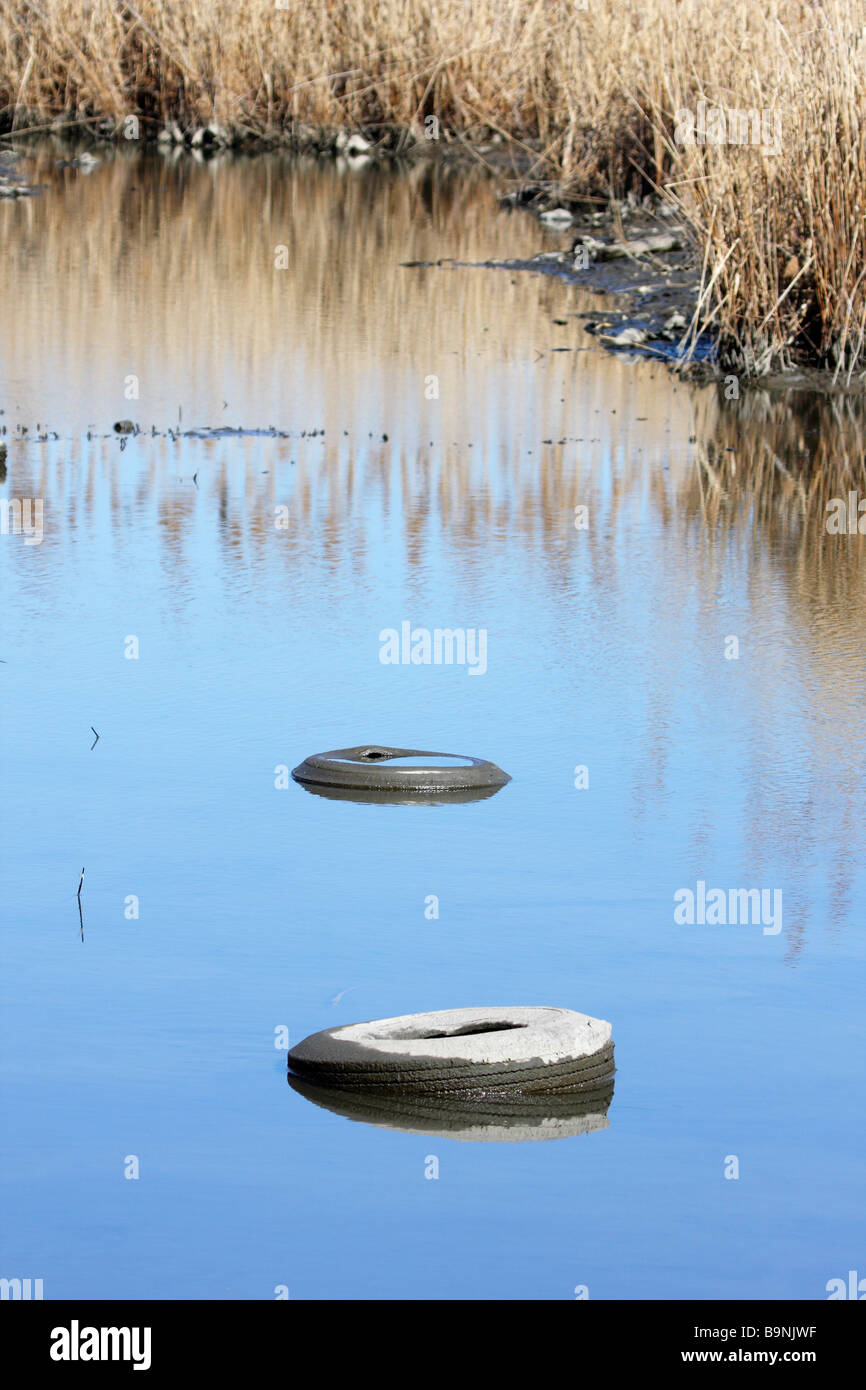 Tires polluting a saltmarsh - Stock Image