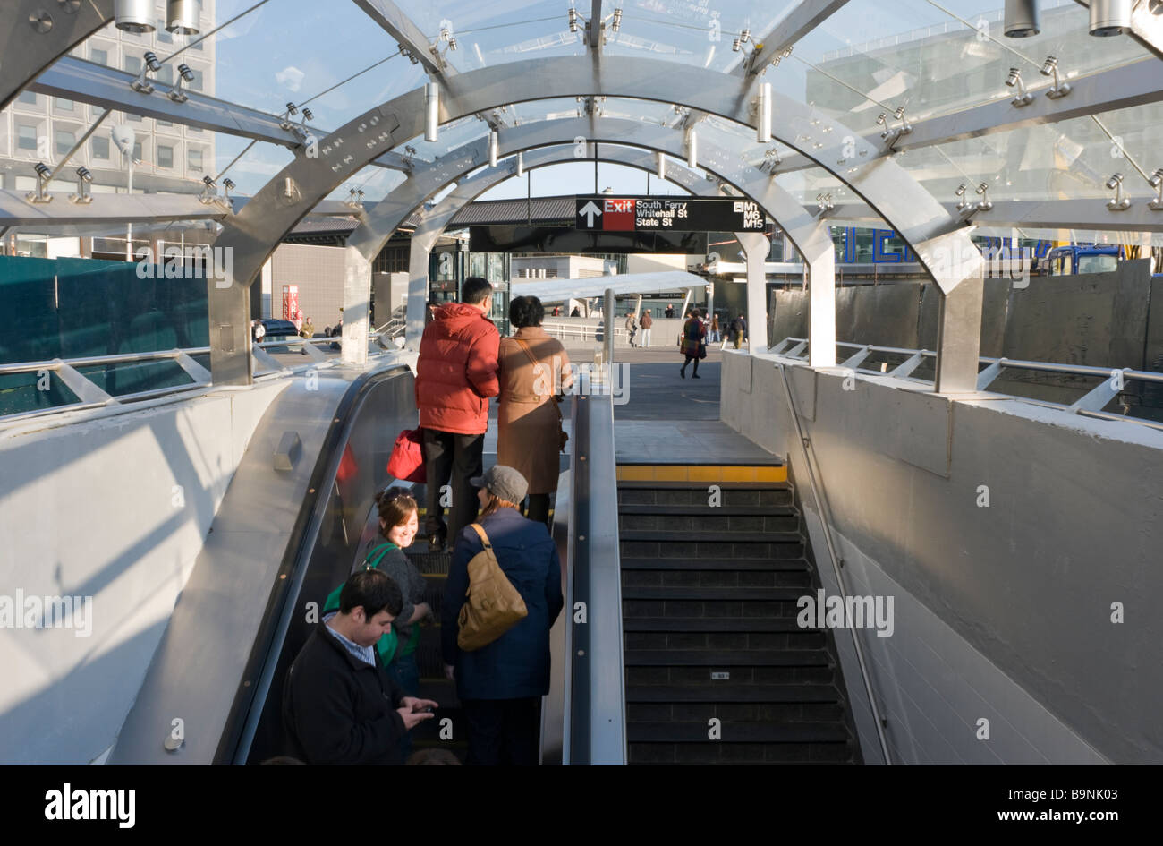 Straphangers on the escalator as they exit the brand new, state of the art, subway station at South Ferry. - Stock Image