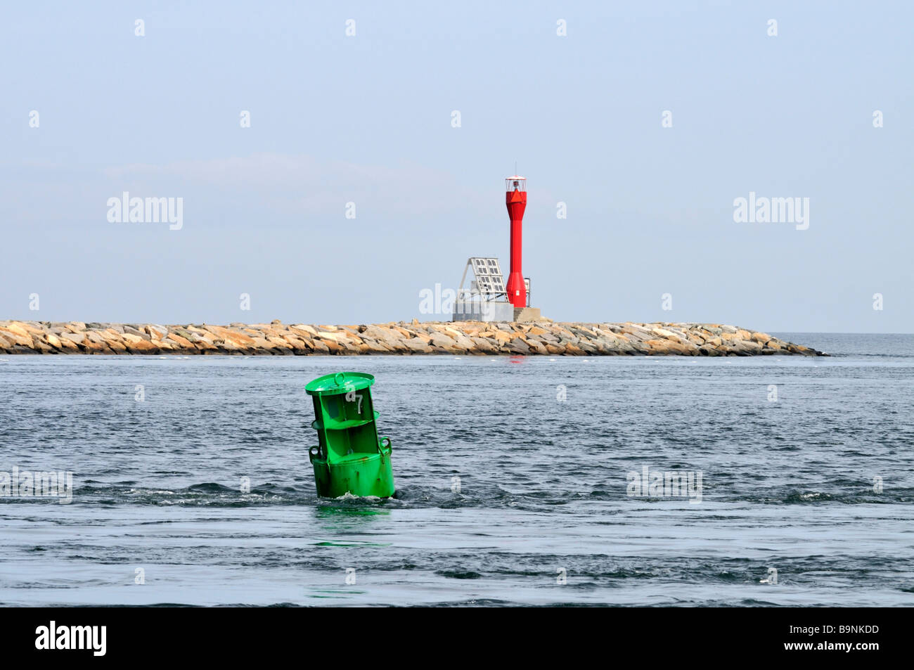 Navigational channel markers in ocean with a green can and a red solar powered daymarker on stone jetty. - Stock Image