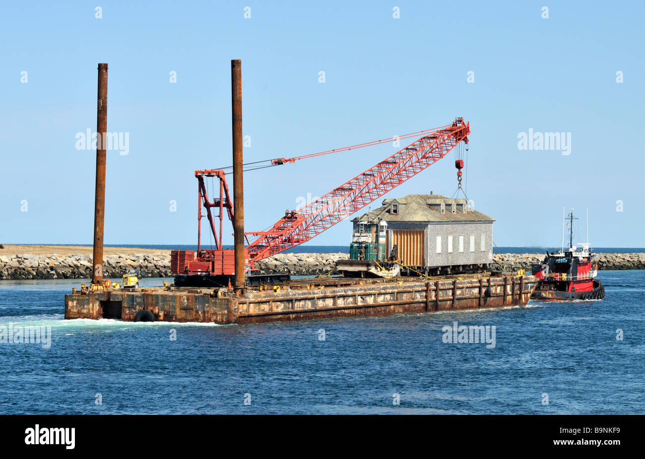 Tugboat pulling a house and crane on a barge Stock Photo: 23218589
