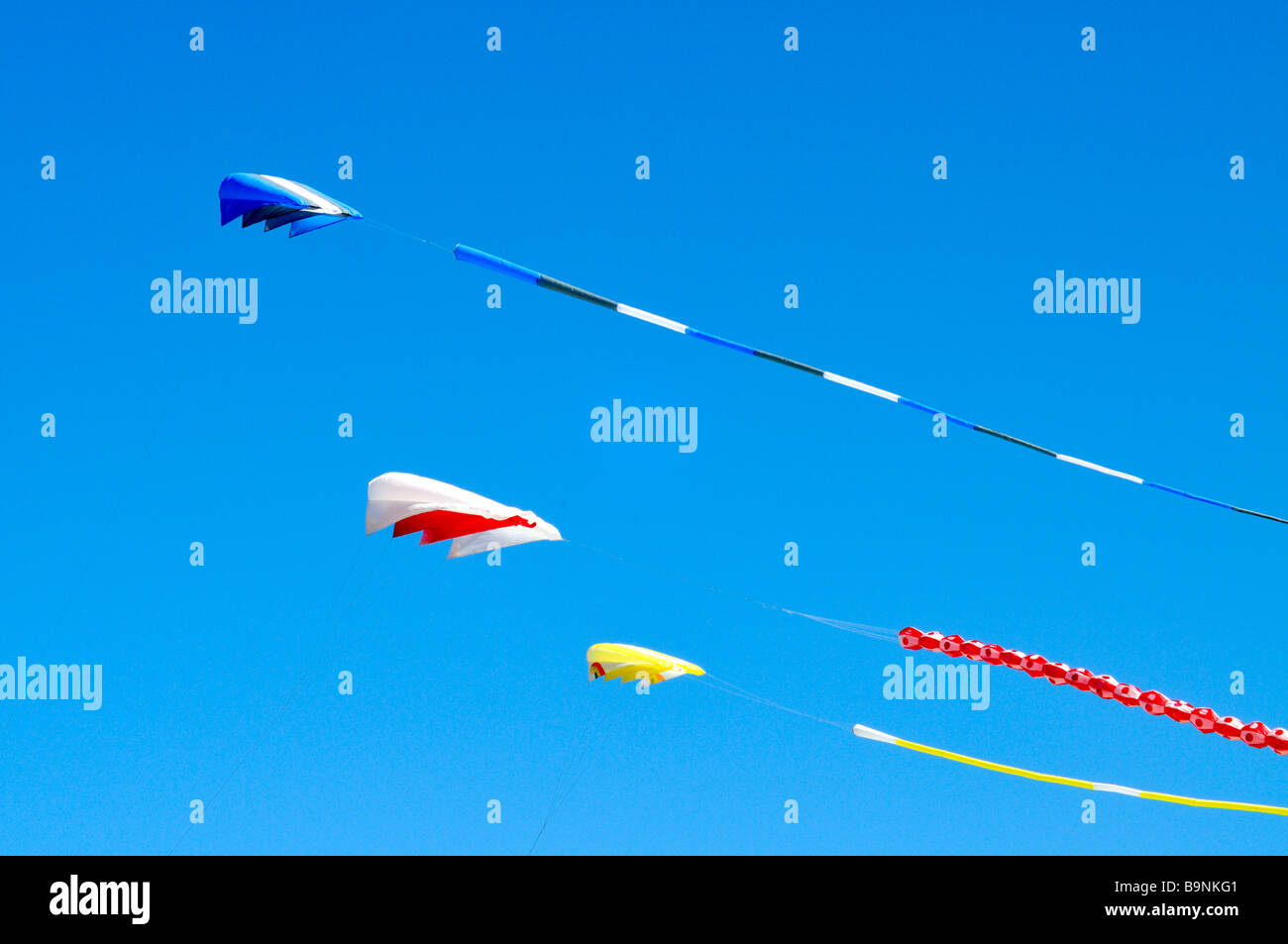 3 three colorful kites flying in the wind against a clear blue sky - Stock Image