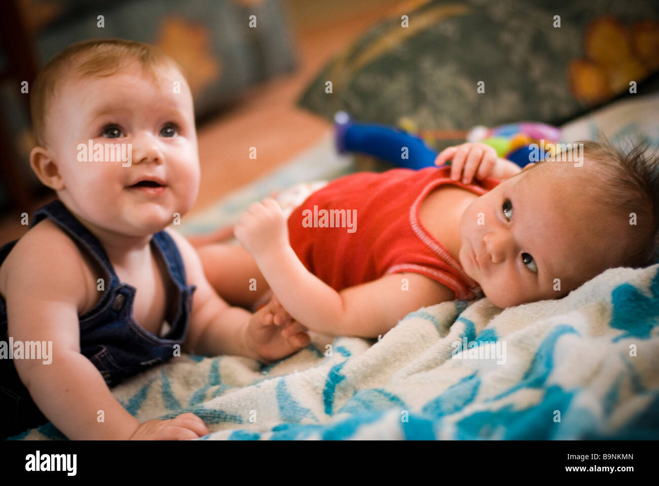Two babies laying on blanket - Stock Image