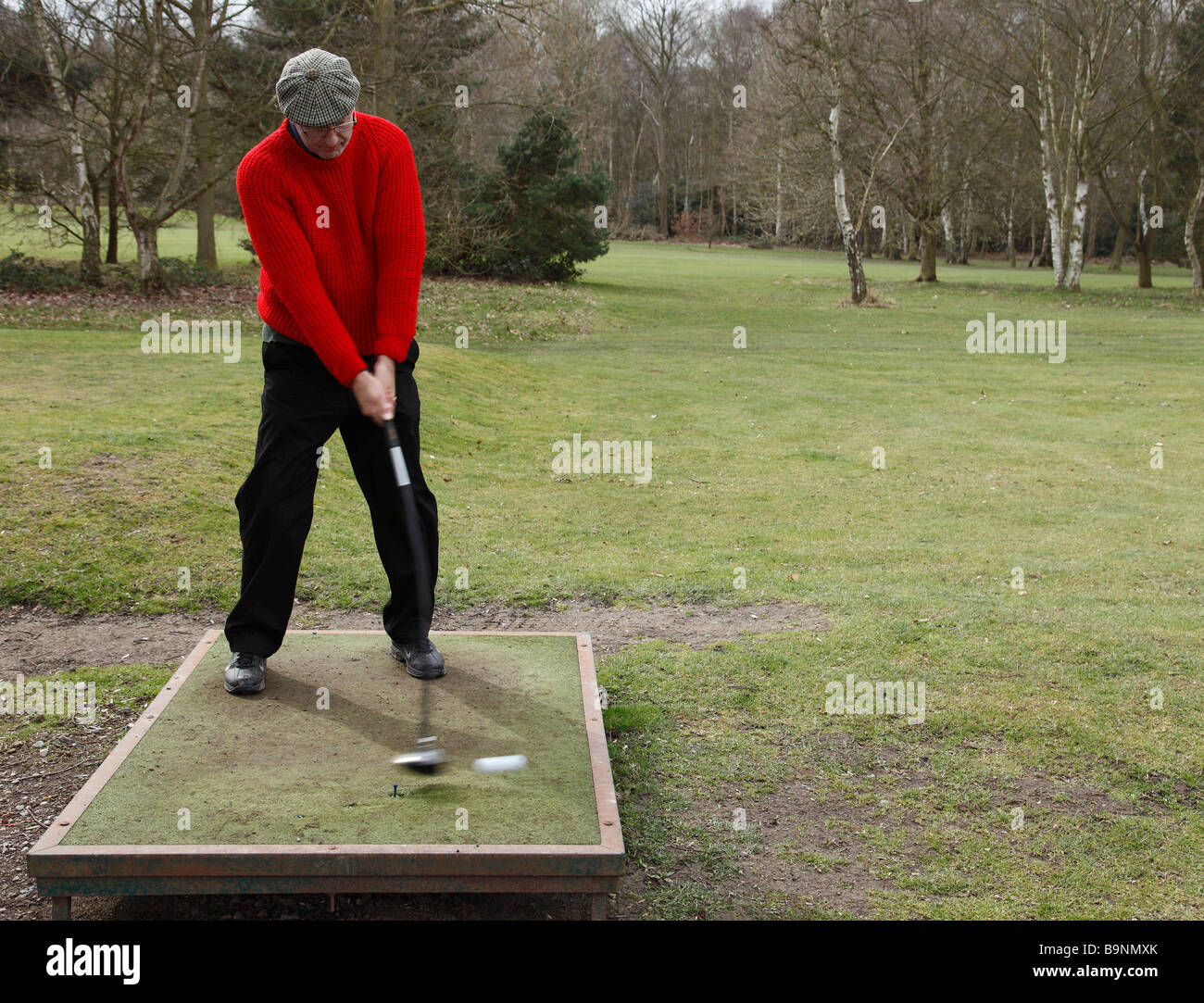 Golfer hitting a ball from a temporary tee. - Stock Image