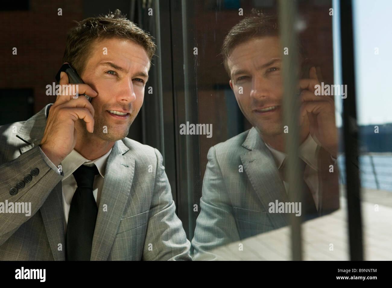 portrait of businessman opposite window talking on mobile phone - Stock Image