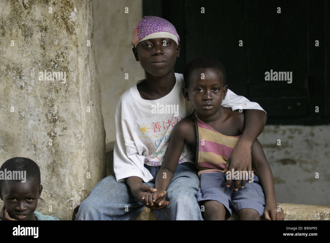 An ex-child soldier with his younger siblings, at a rehabilitation centre in the north of Liberia - Stock Image