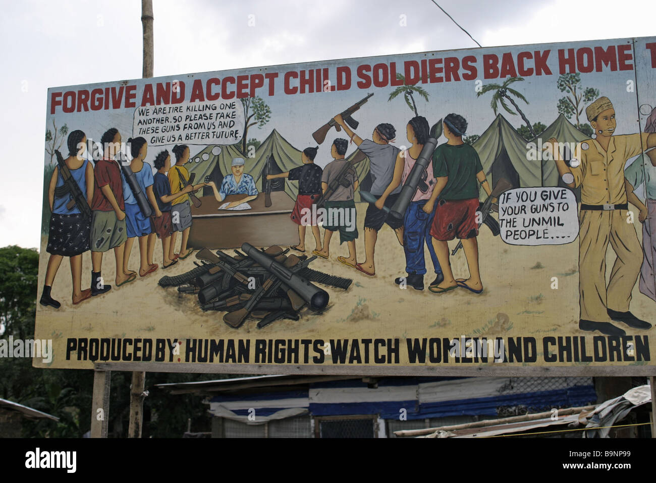 At a camp for war refugees in Liberia, a poster urges fighters and rebels to hand in their weapons to the United - Stock Image