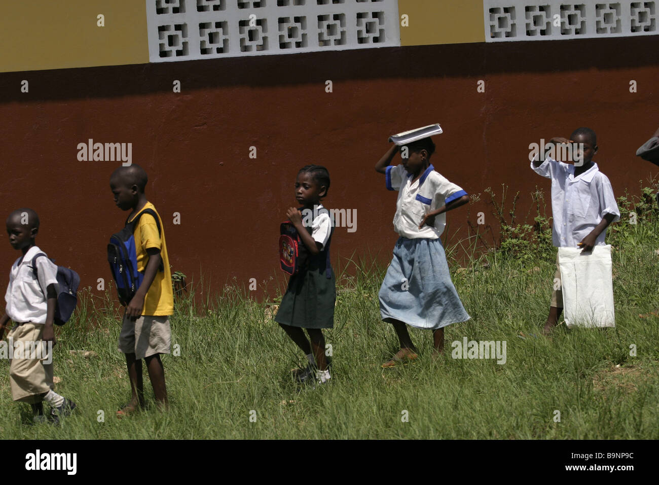 A group of young school children head towards a classroom at a school in northern Liberia - Stock Image