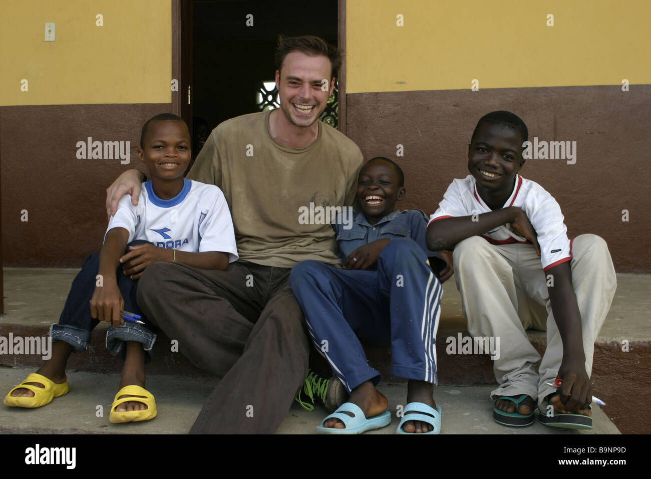TV and radio presenter Jamie Theakston poses for photographs with ex-child combatants/soldiers in Liberia - Stock Image