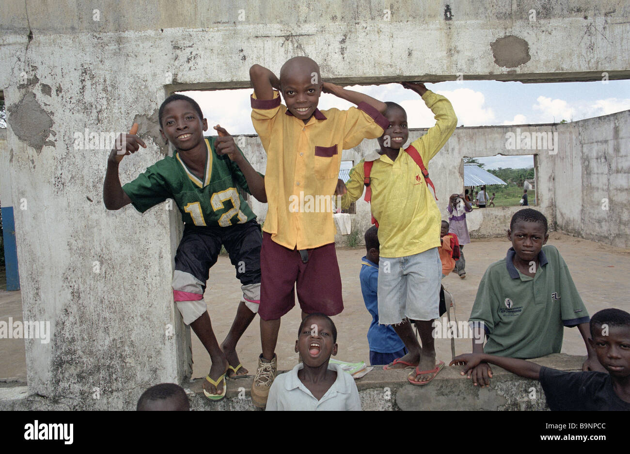 School boys in Liberia pose for the camera at their war damaged school in the north of the country - Stock Image