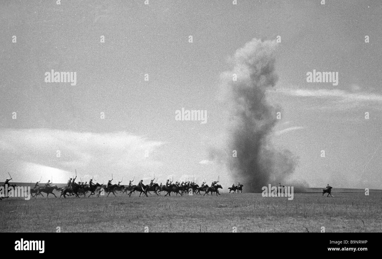 A cavalry unit galloping across a field An explosion - Stock Image