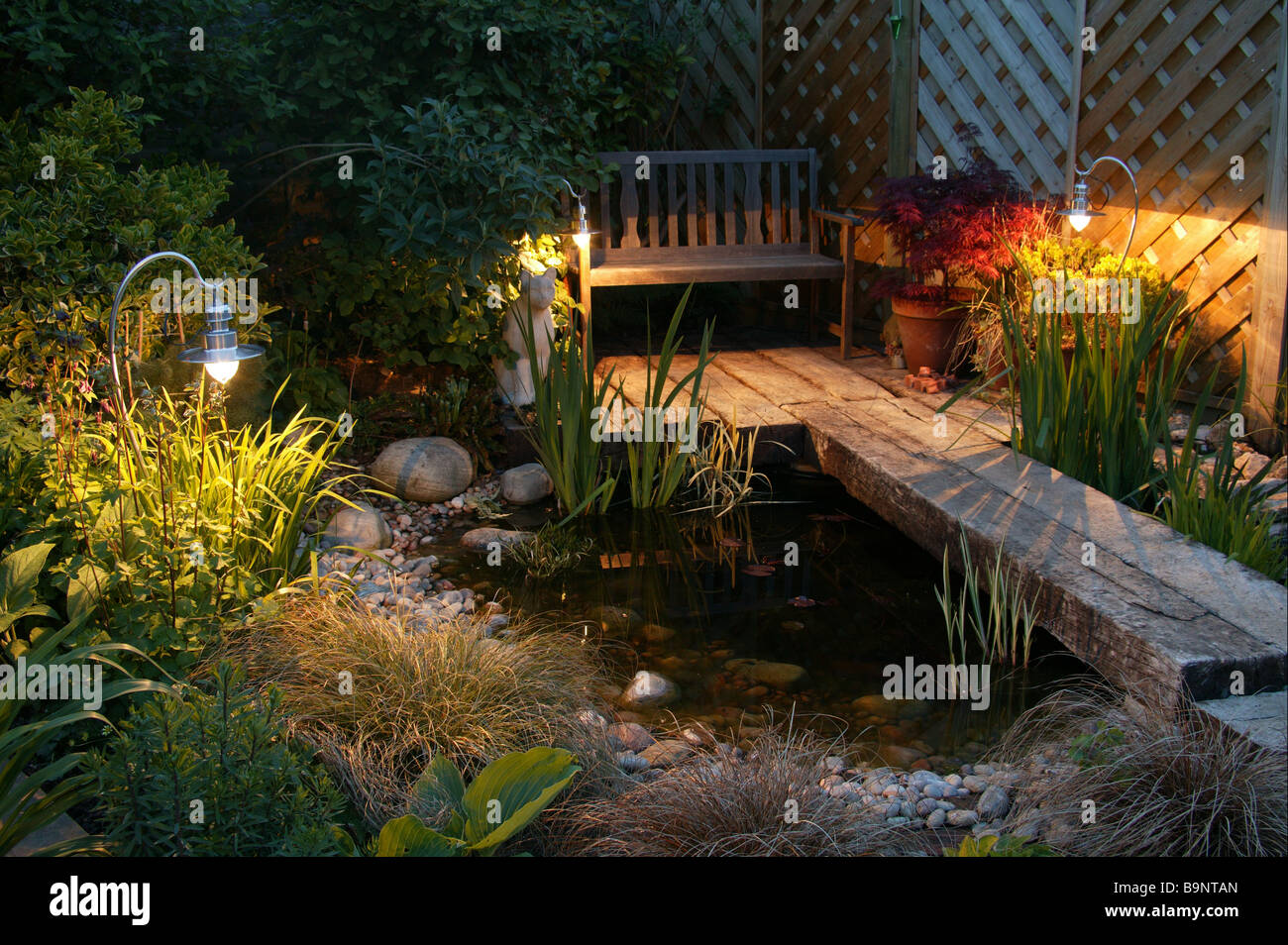 Early evening british garden in the summer, features a pond, garden chair, lights and stone detail. - Stock Image
