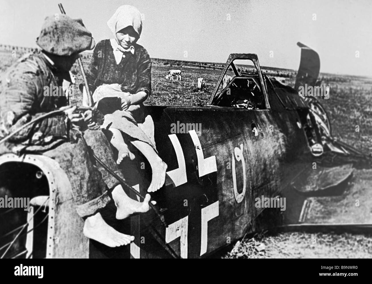 Village children sitting on the fuselage of a downed Nazi plane in the field - Stock Image