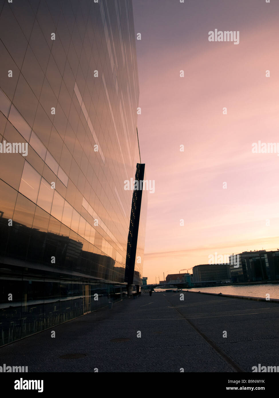 Sunrise in Copenhagen, Denmark.  The Royal Library (the Black Diamond) towers to the left, blending into the morning Stock Photo