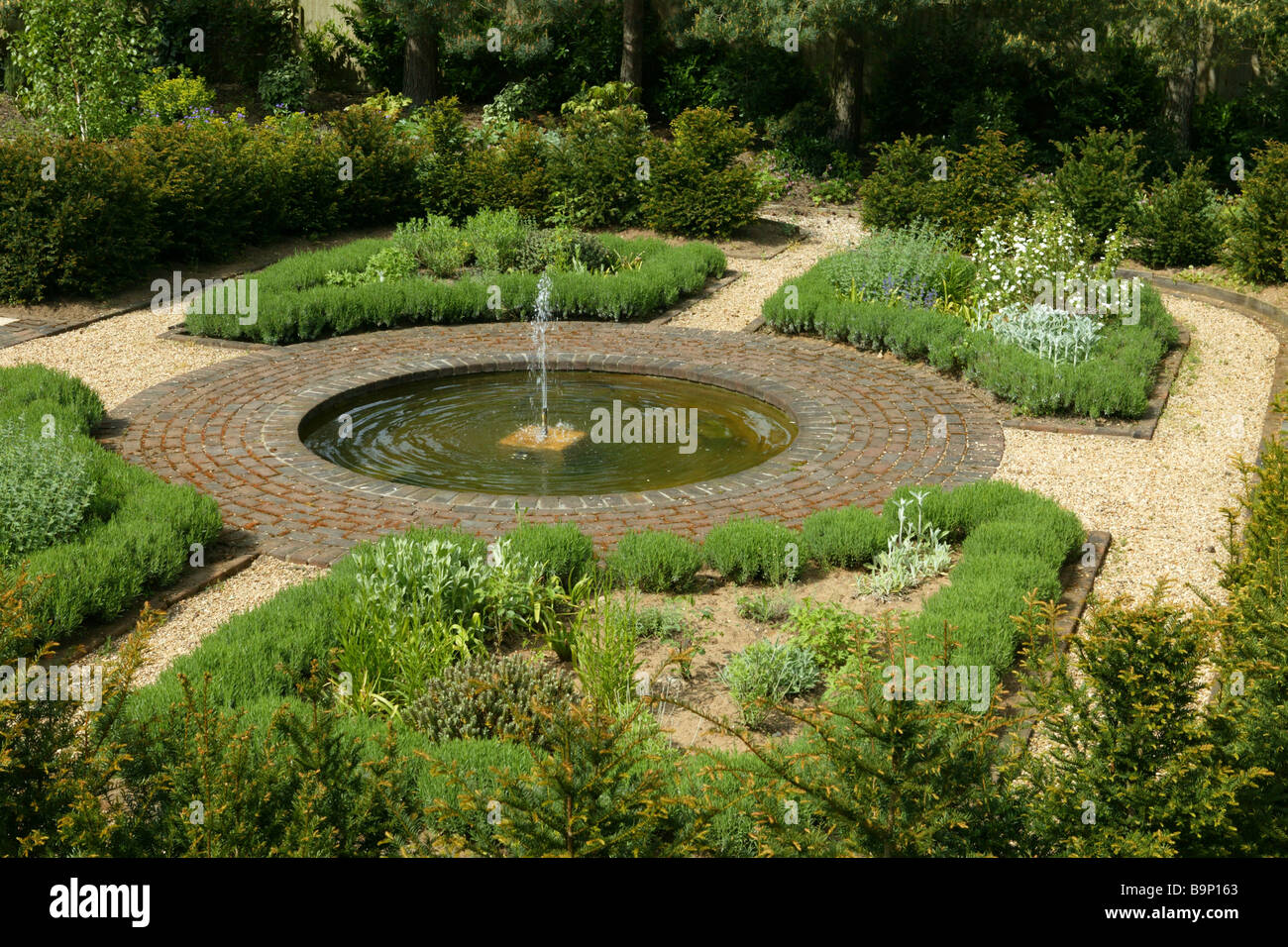 English country garden, landscaped with gravel and borders, and a central water feature of a circular fountain. - Stock Image