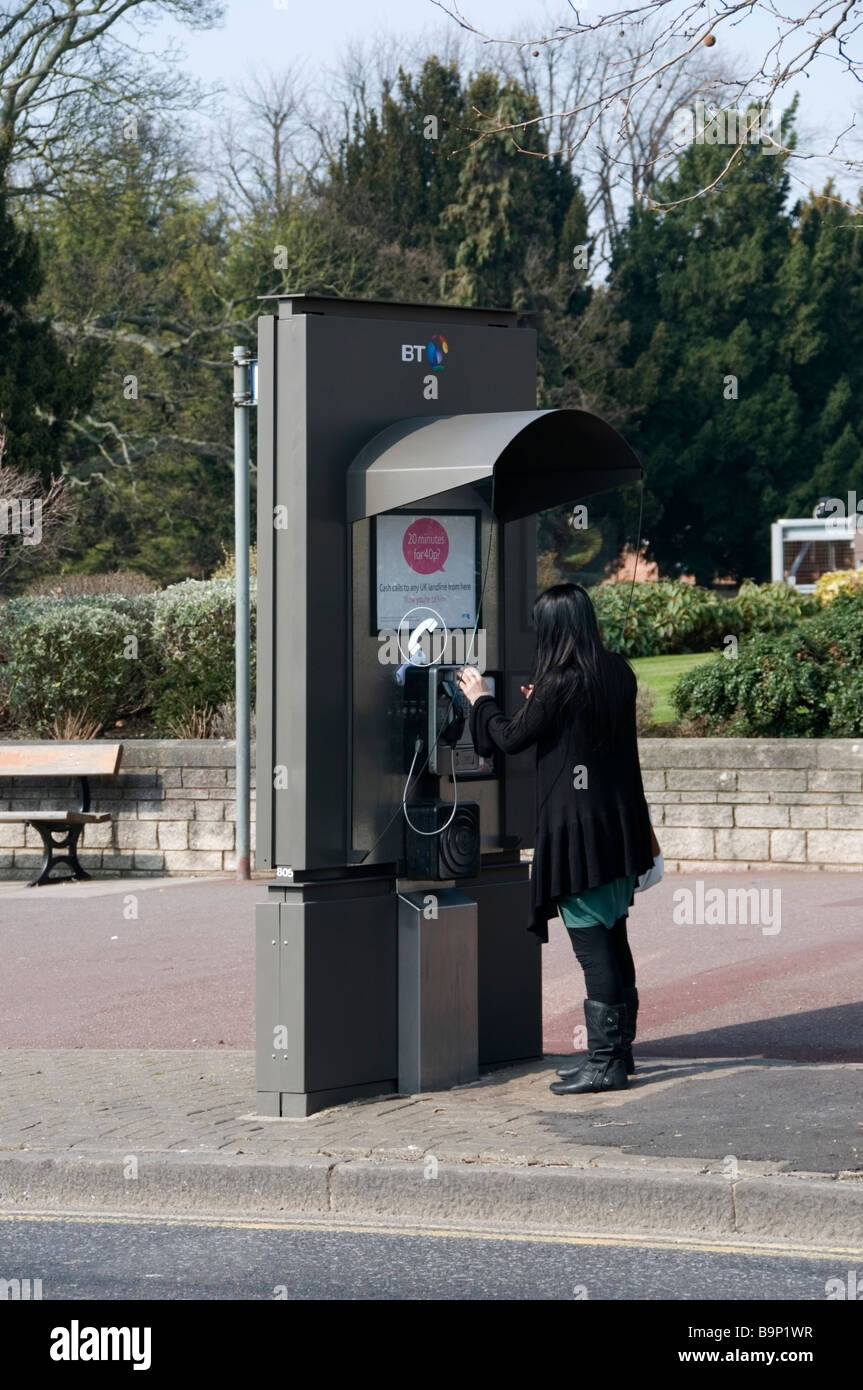 Essex Girl with long black hair using public street BT telephone box, making a call, Romford, Essex, UK, Europe, - Stock Image