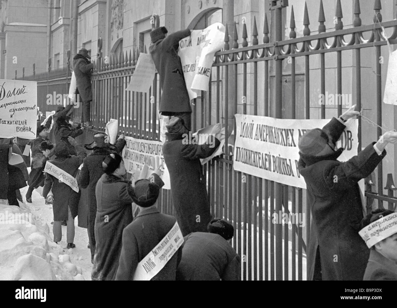 Marchers hanging out placards outside the American embassy to protest American air raids on populated localities - Stock Image