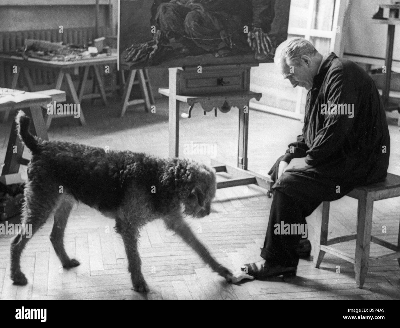 Soviet artist Pavel Korin playing with a dog In his studio - Stock Image