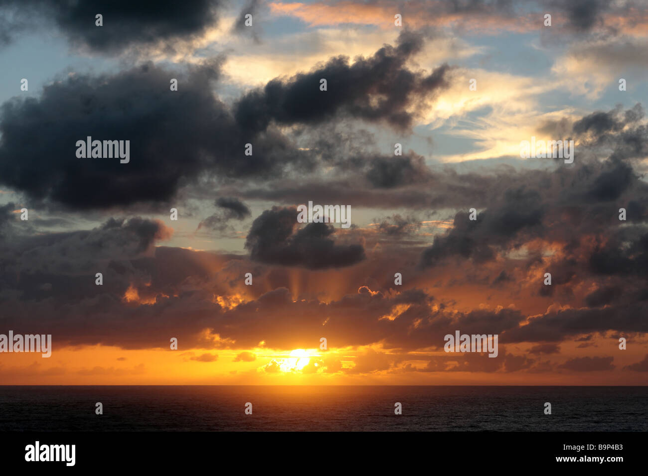 Sunrise over the pacific ocean with varying cloudscapes - Stock Image