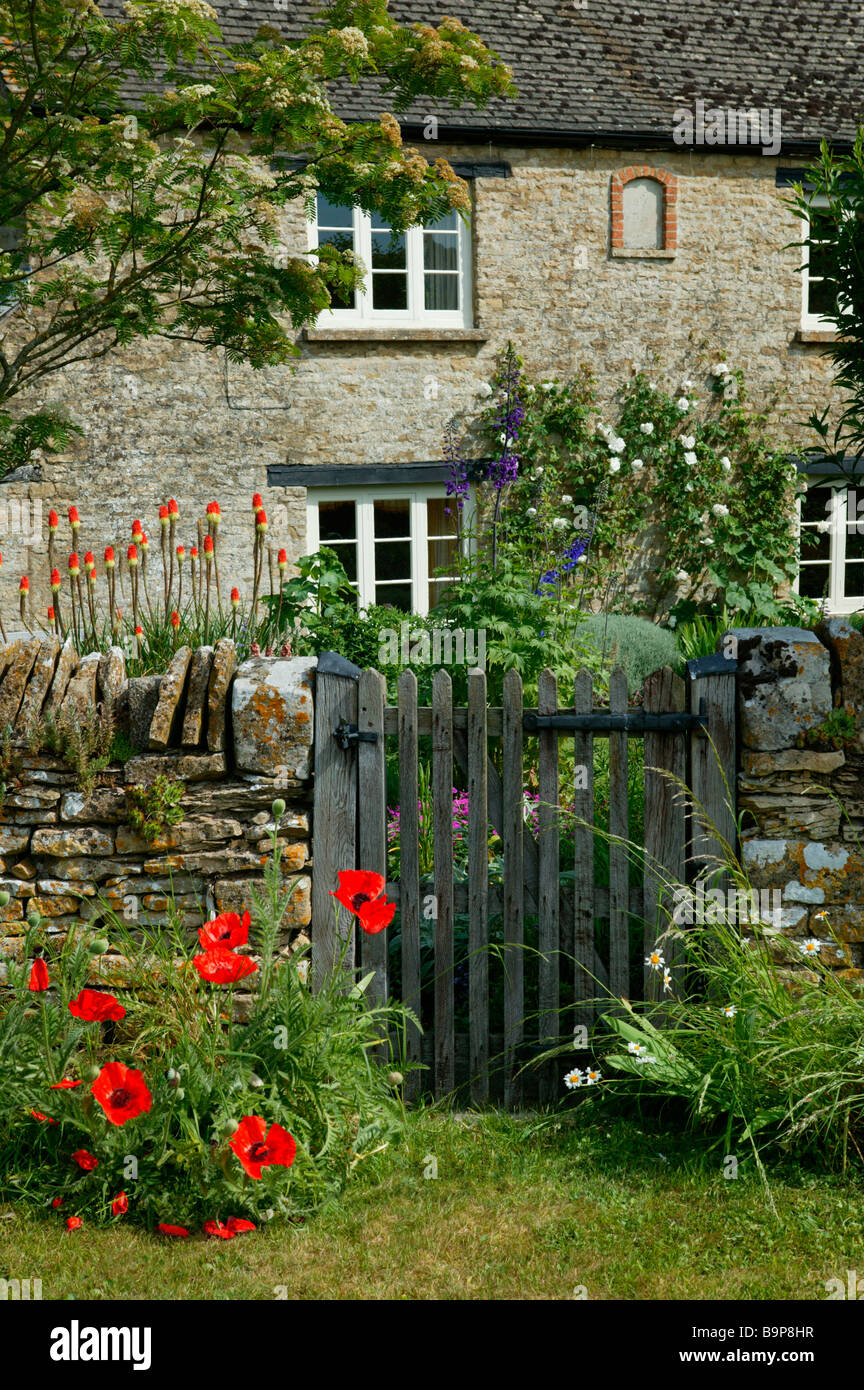 An english country cottage. Poppy flowers and gate in foreground. With flowers growing up the outside. - Stock Image