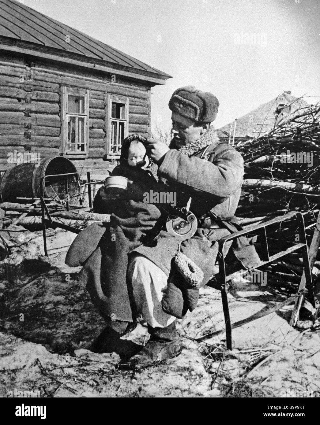 A soldier holding a child whose mother was killed - Stock Image