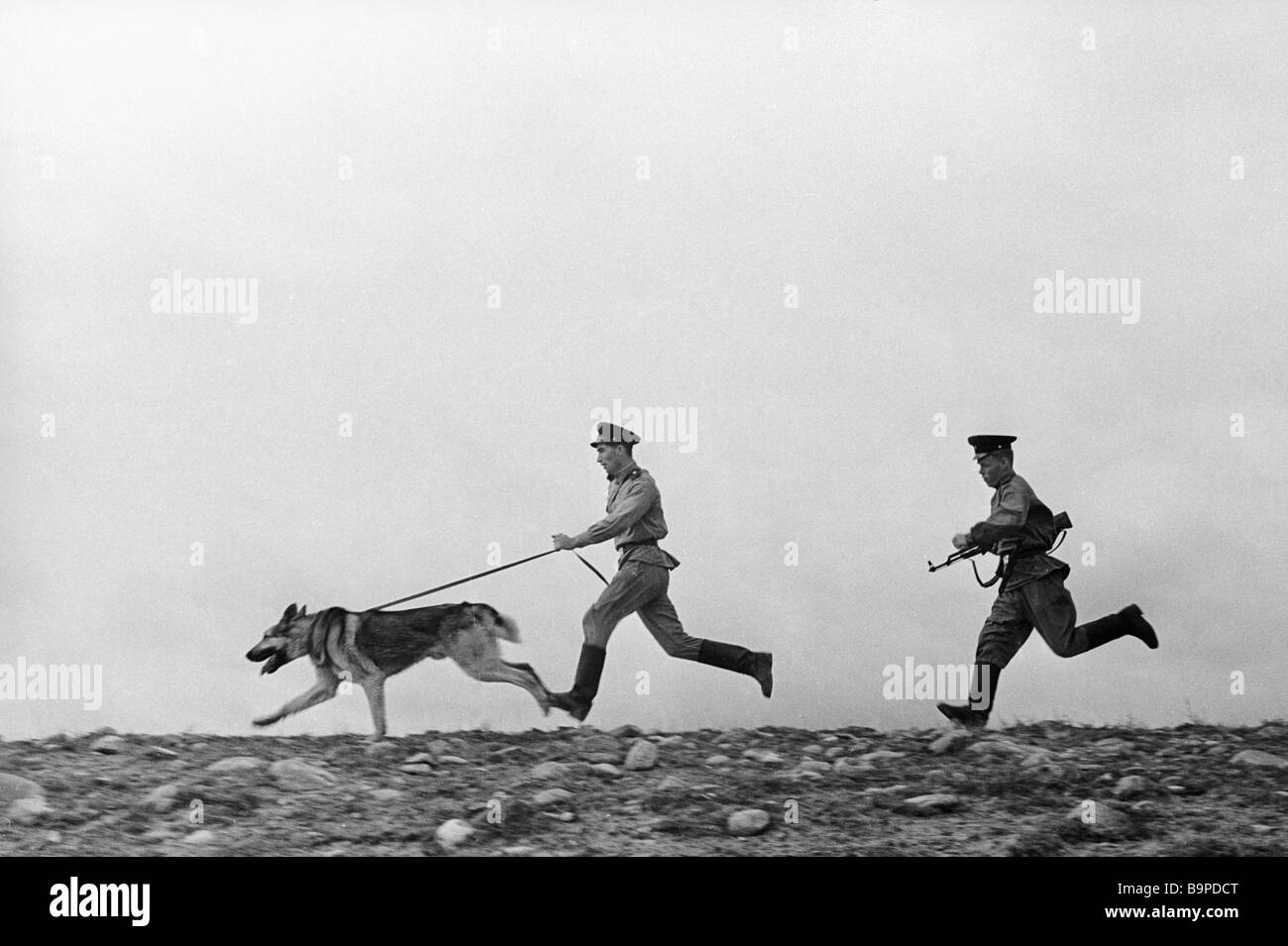 Frontier guards on duty pursuing a trespasser with their dog - Stock Image