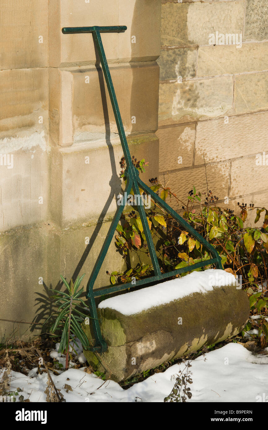 Traditional old stone garden roller in winter - Stock Image