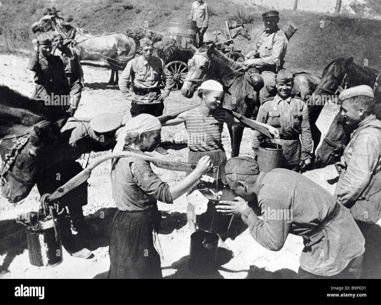 Women carrying water smiling to Soviet soldiers liberators One of them drinking from a bucket - Stock Image