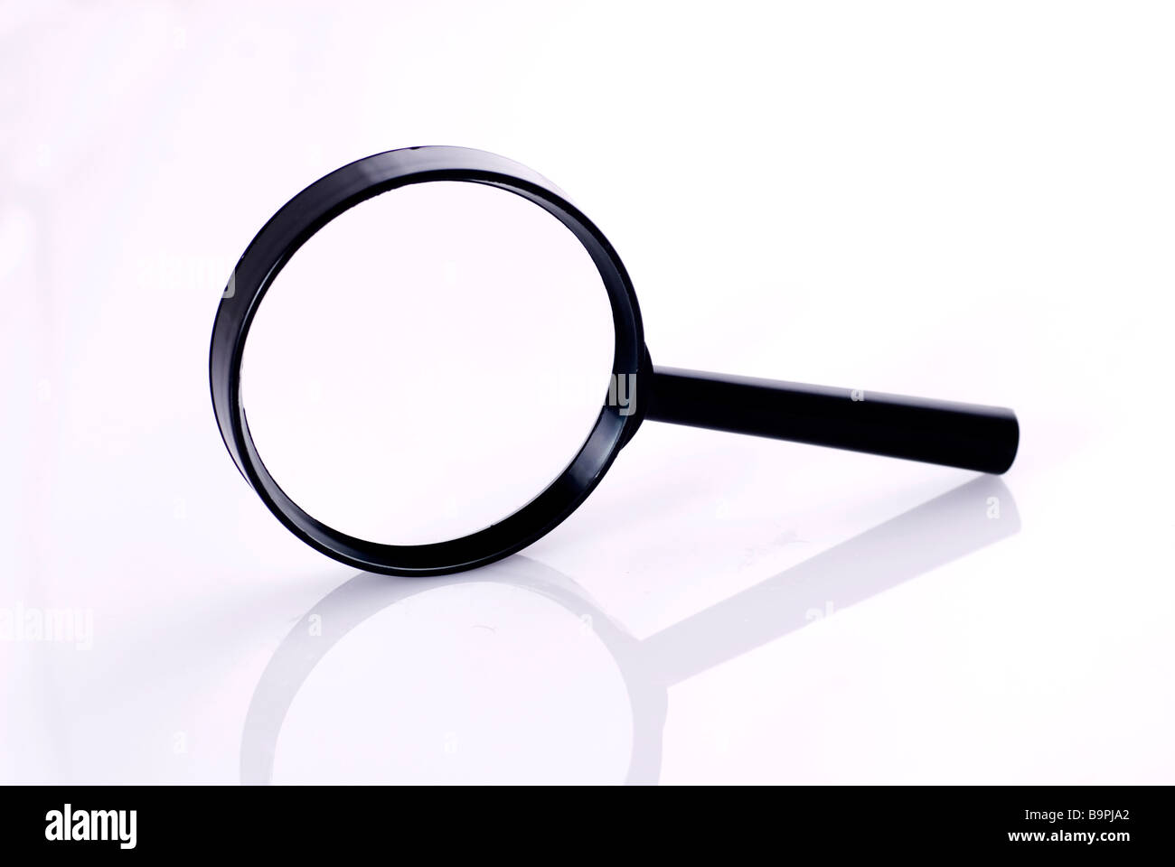 Side view of a magnifying glass on a white background - Stock Image