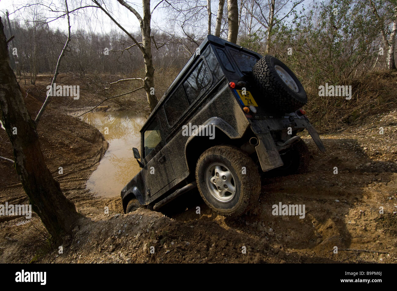 A Land Rover Defender 90 creeps down a steep bank - Stock Image