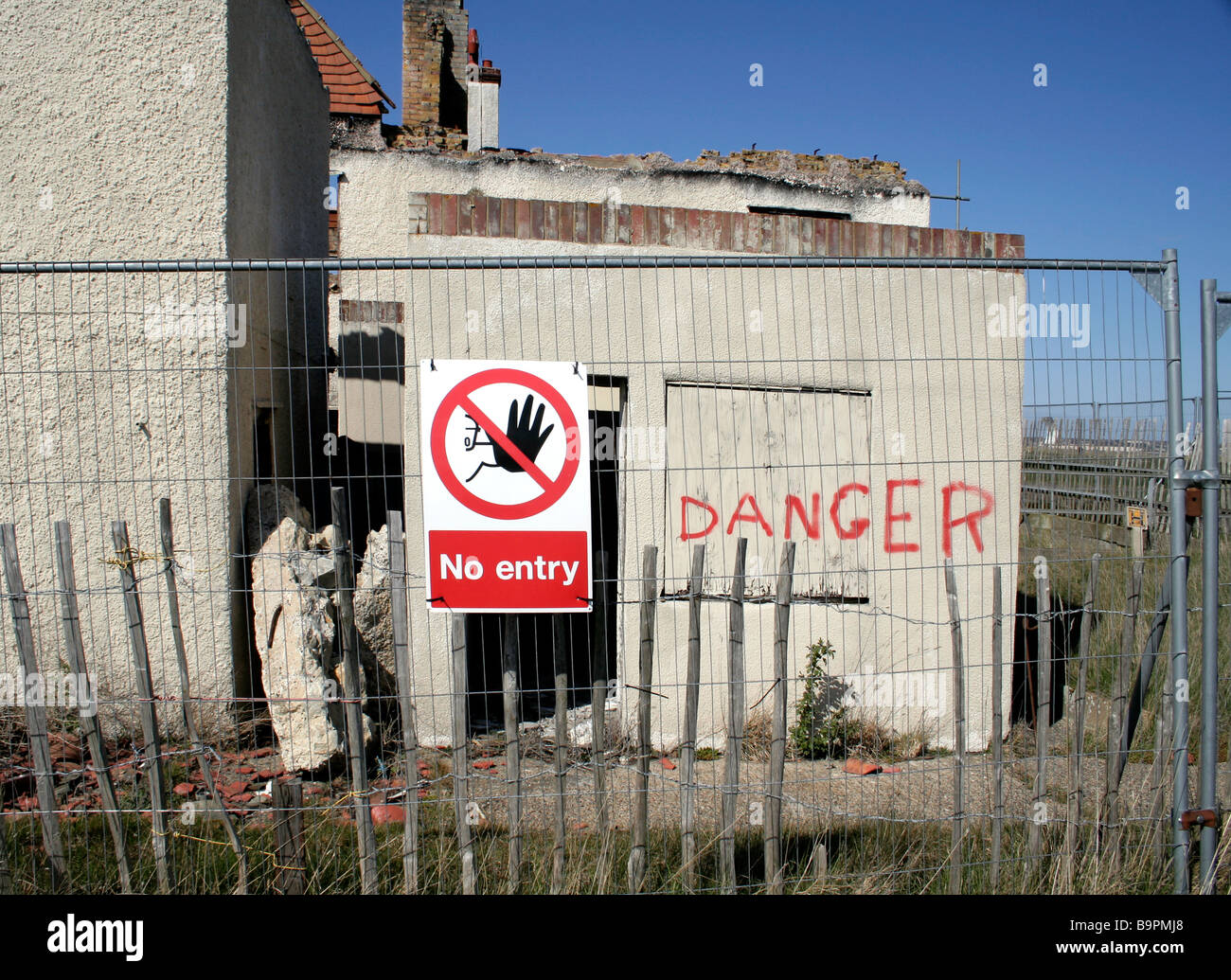 Warning sign attached to fencing outside a burnt out derelict building. It reads ' No entry' - Stock Image