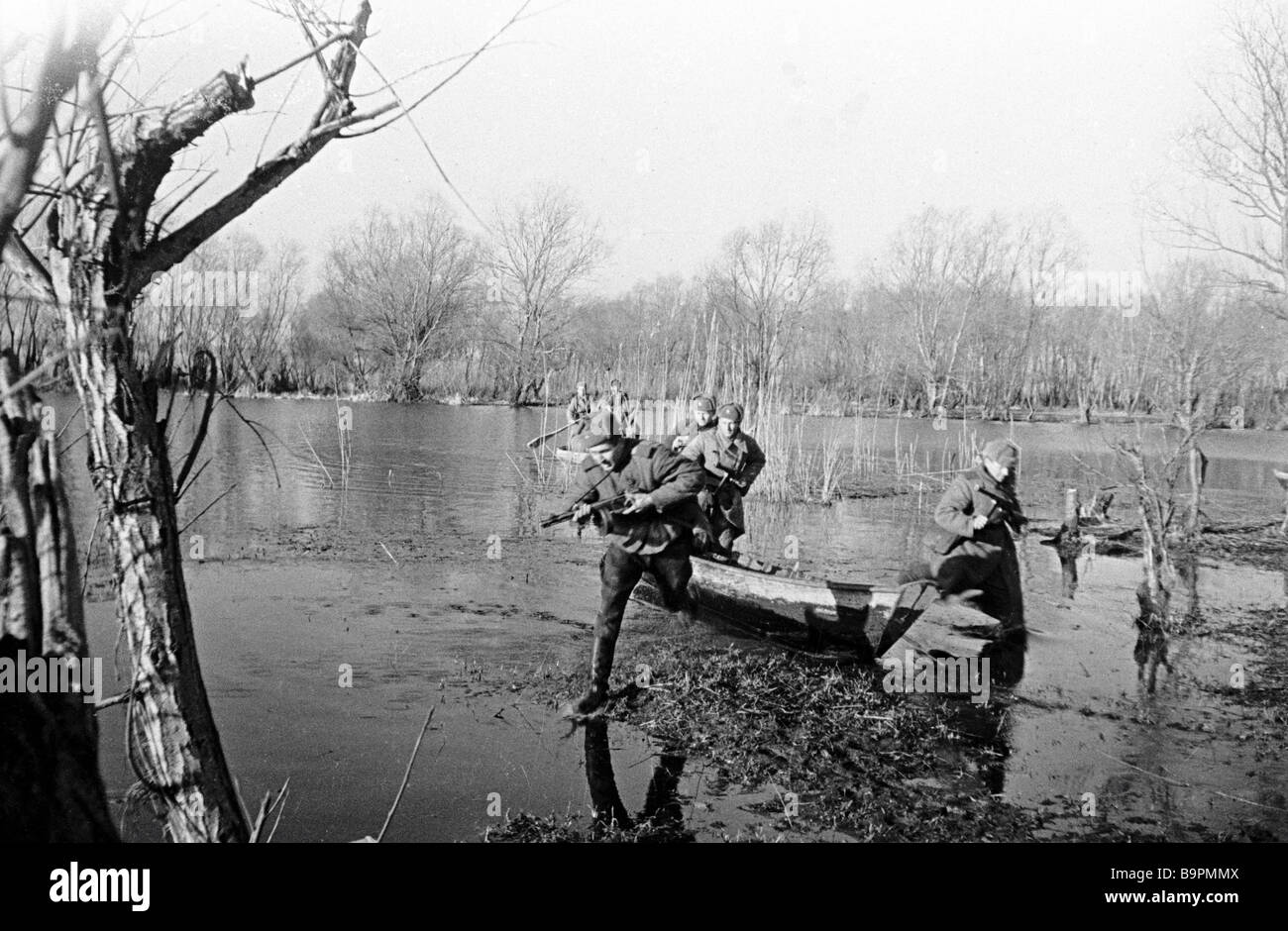 Soldiers with rifles making their way in water - Stock Image