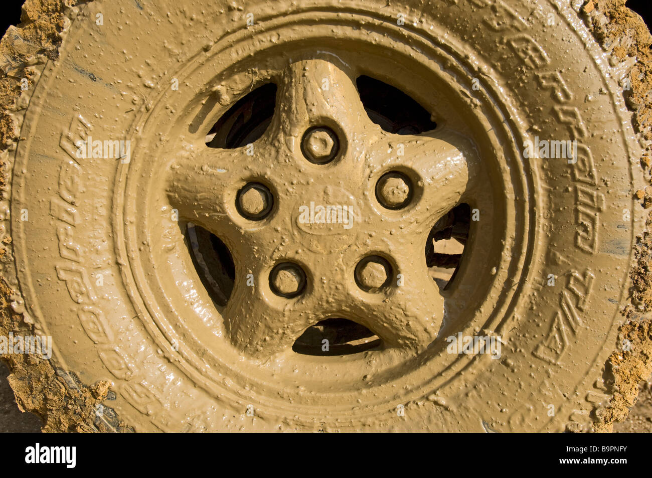 The muddy wheel of a Land Rover Defender 90 after driving through a flooded road - Stock Image
