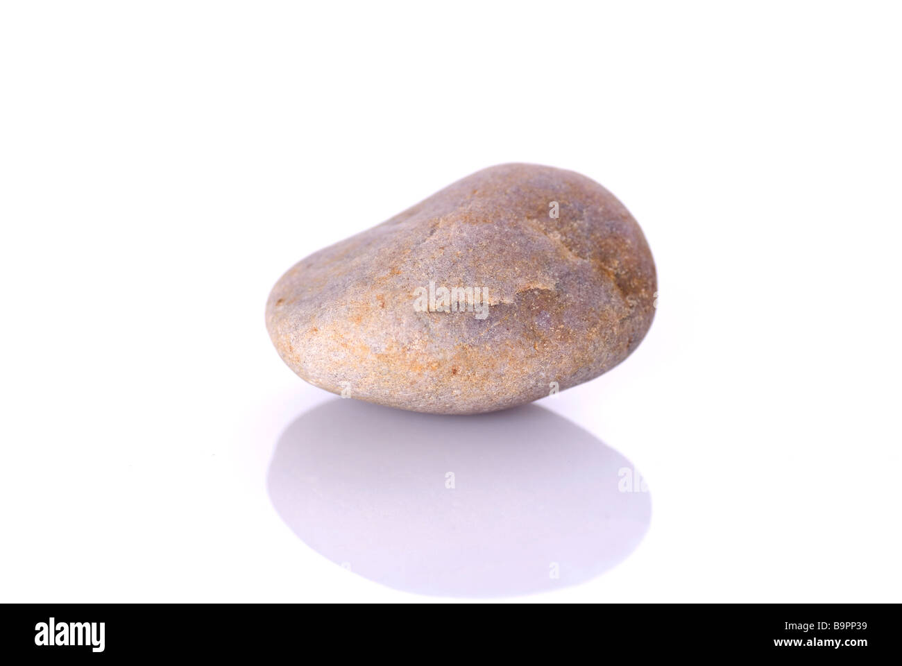 One pebble isolated against a white background - Stock Image