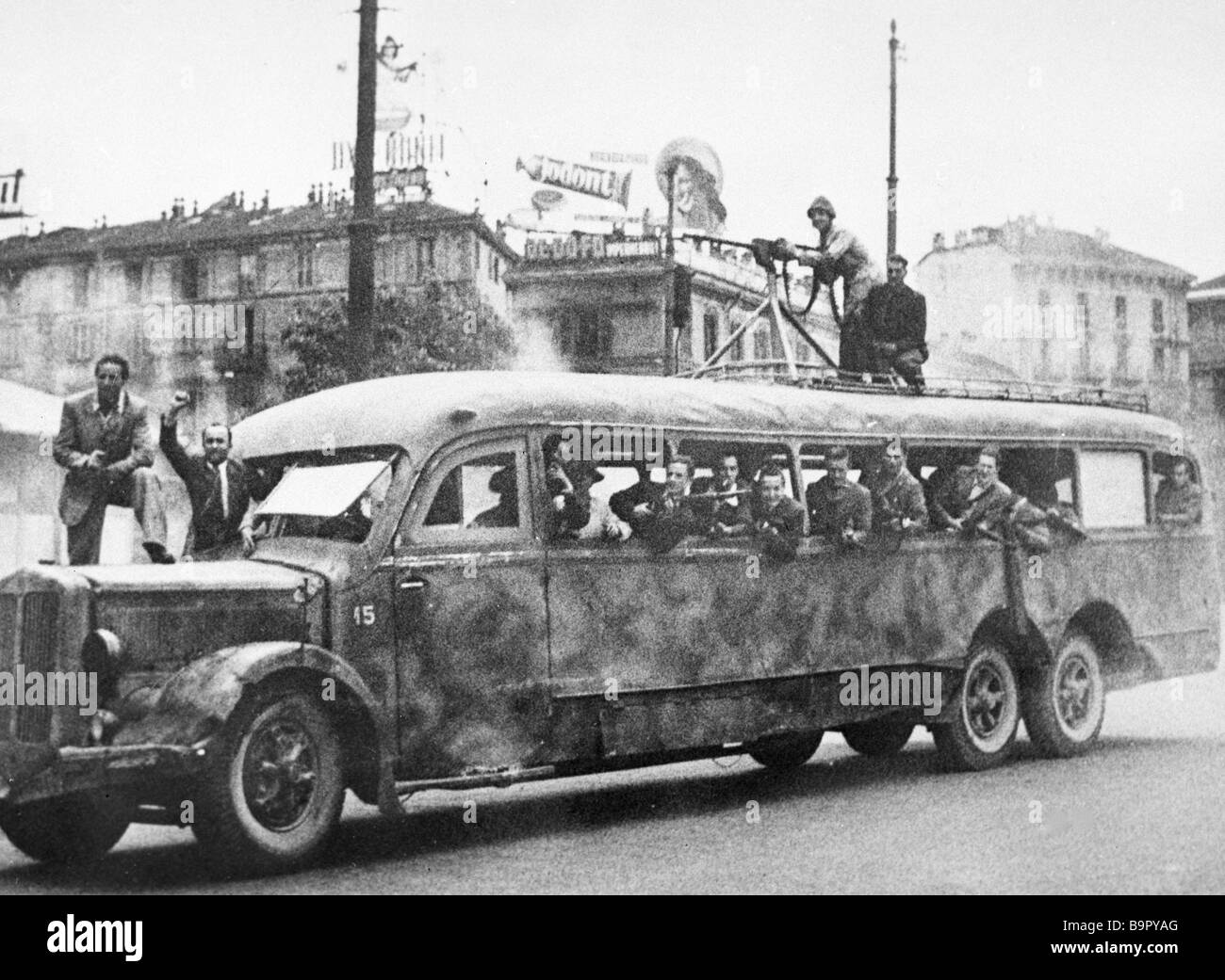 Armed group of the Resistance movement in a military bus on a Milan street during WWII Stock Photo