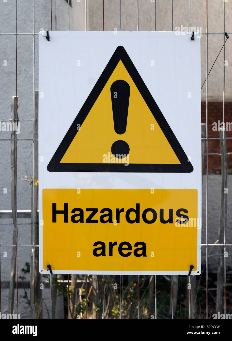 Warning sign attached to fencing outside a burnt out derelict building. It reads 'Hazardous area' - Stock Image