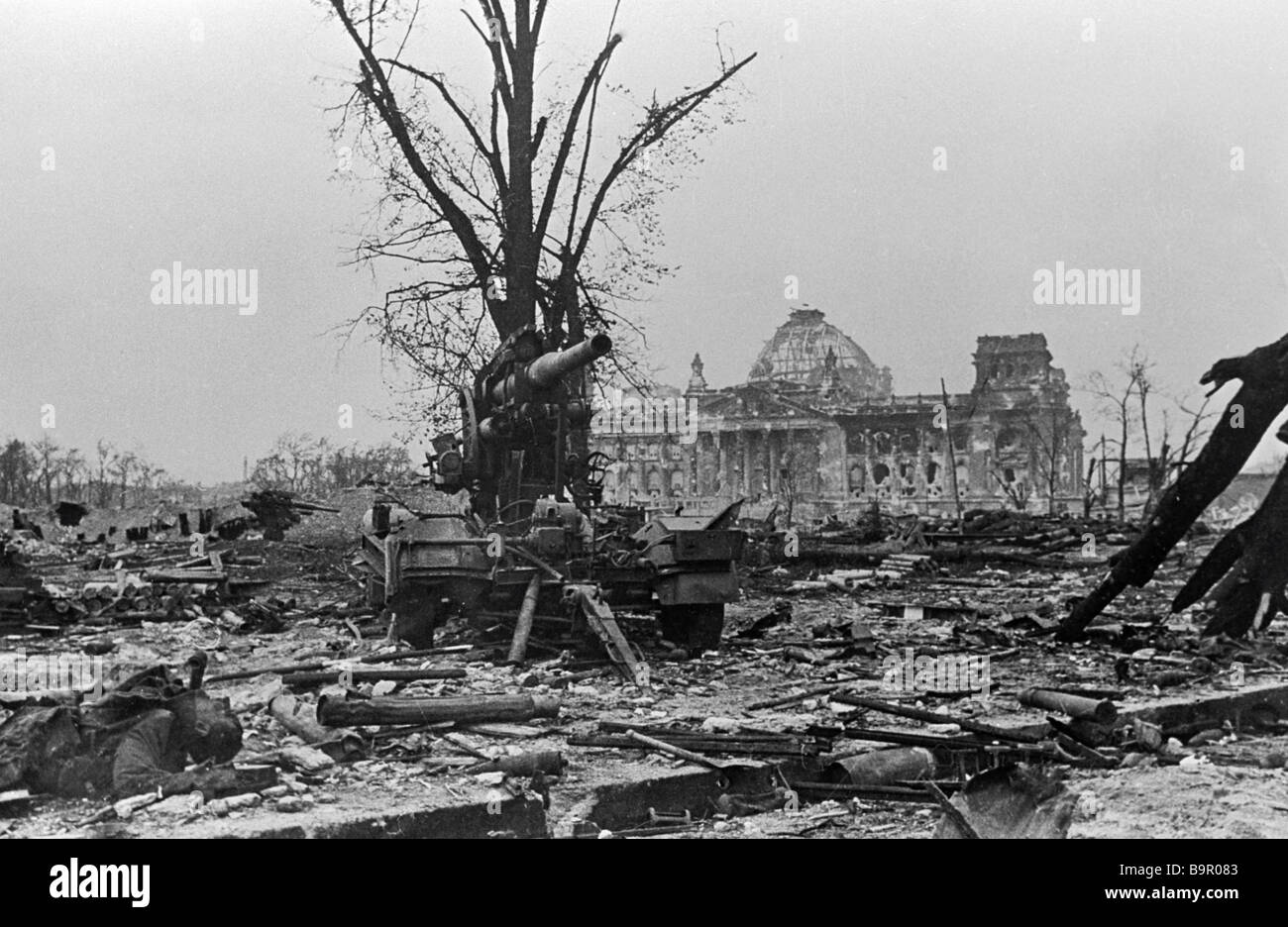 An artillery gun and a killed soldier against the background of the destroyed Reichstag and dead trees - Stock Image